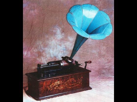 """Analisi storica ed artistica: Fonografo """"Edison-Ome"""" con tromba a giglio in ferro azzurra, completo di coperchio. Epoca: Anno 1898 circa."""